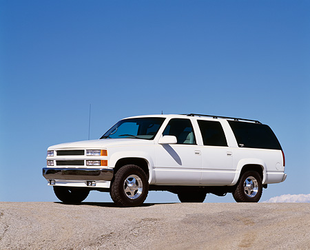 AUT 15 RK0246 04 © Kimball Stock 1995 Chevrolet Canepa Suburban White 3/4 Side View On Pavement Hill Blue Sky