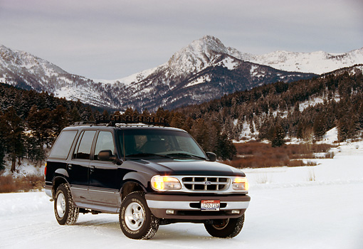 AUT 15 RK0270 02 © Kimball Stock 1996 Ford Explorer Black Front 3/4 View On Snow By Mountains