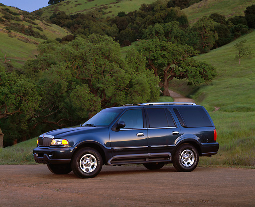 AUT 15 RK0307 01 © Kimball Stock 2000 Lincoln Navigator Blue Side 3/4 View On Dirt By Grass Hill And Trees At Dusk