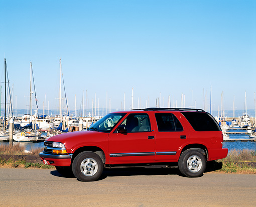 AUT 15 RK0310 01 © Kimball Stock 2000 Chevrolet Blazer Red 3/4 Front View On Pavement By Harbor Blue Sky