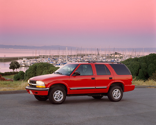 AUT 15 RK0314 03 © Kimball Stock 2000 Chevrolet Blazer Red 3/4 Front View On Pavement Harbor Background