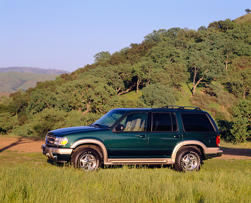 AUT 15 RK0317 06 © Kimball Stock 2000 Ford Explorer Green And Gold 3/4 Front View On Grass Trees Background