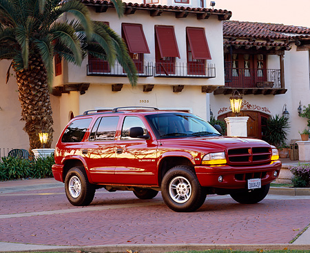 AUT 15 RK0323 02 © Kimball Stock 2000 Dodge Durango Burgundy Side 3/4 View By Spanish Building At Dusk