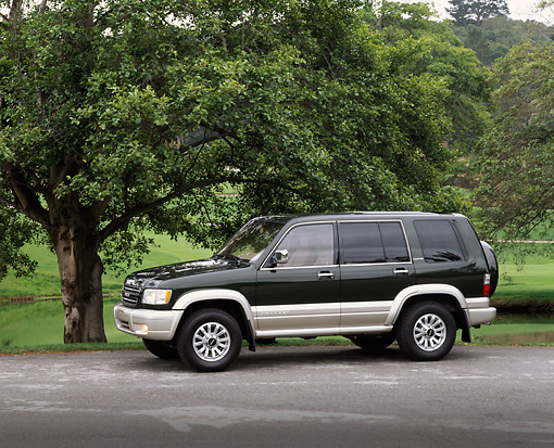 AUT 15 RK0331 01 © Kimball Stock 2000 Isuzu Trooper Green 3/4 Front View By Trees