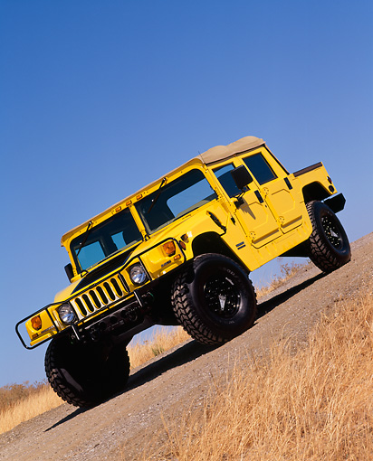AUT 15 RK0353 10 © Kimball Stock 2000 Hummer H1 Competition Yellow Slanted Front 3/4 View On Pavement Hill Dry Grass Blue Sky