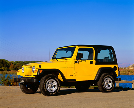 AUT 15 RK0394 01 © Kimball Stock 2000 Jeep Wrangler Sport Hardtop Yellow 3/4 Side View On Pavement Blue Sky