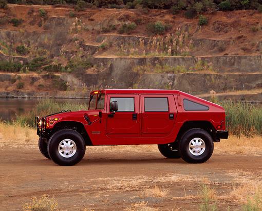 AUT 15 RK0396 02 © Kimball Stock 2000 Hummer H1 Slantback Red 3/4 FrontView On Dirt By Quarry