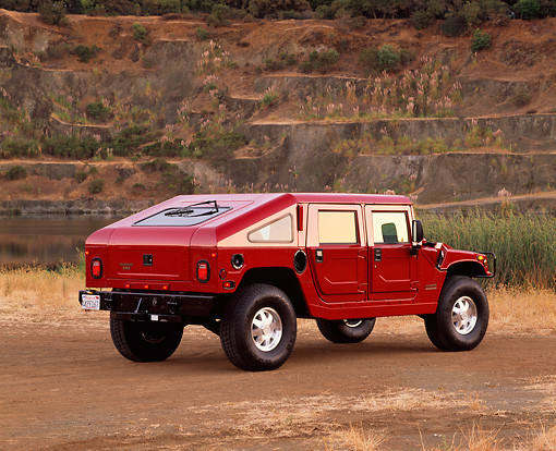 AUT 15 RK0400 09 © Kimball Stock 2000 Hummer H1 Slantback Red Rear 3/4 View On Dirt By Quarry