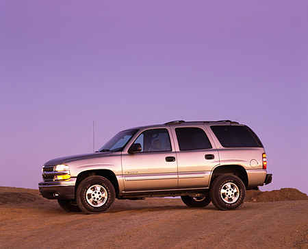 AUT 15 RK0419 02 © Kimball Stock 2000 Chevrolet Tahoe 4WD Pewter 3/4 Side View On Pavement Hill At Dusk