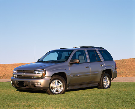AUT 15 RK0530 05 © Kimball Stock 2002 Chevy Trailblazer LTZ 4WD Pewter 3/4 Front View On Grass Blue Sky