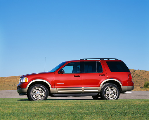 AUT 15 RK0549 01 © Kimball Stock 2002 Ford Explorer Burgundy Profile View On Grass Blue Sky