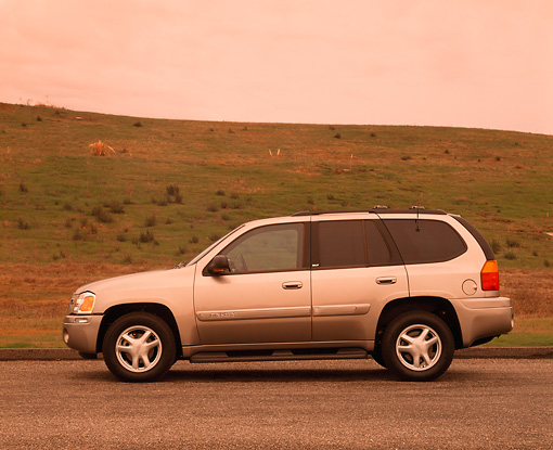 AUT 15 RK0558 03 © Kimball Stock 2002 GMC Envoy Champagne Profile View On Pavement By Grass Hill Filtered