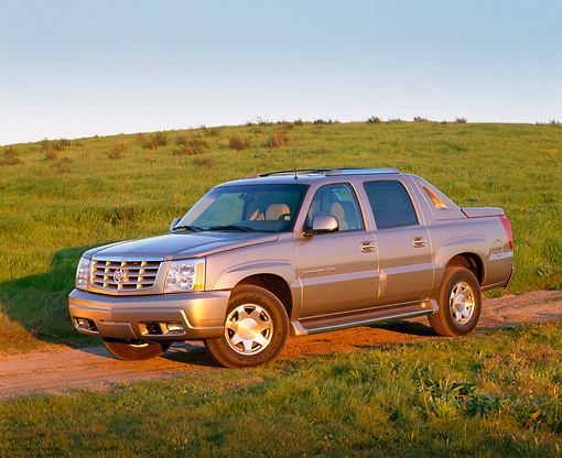 AUT 15 RK0576 01 © Kimball Stock 2002 Cadillac Escalade EXT Silver Sand 3/4 Side View On Grass Hill Blue Sky