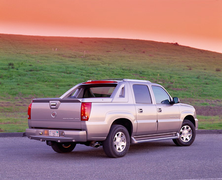 AUT 15 RK0583 05 © Kimball Stock 2002 Cadillac Escalade EXT Silver 3/4 Rear View On Pavement By Grass Hill Filtered
