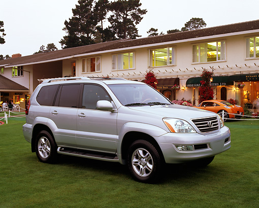 AUT 15 RK0606 02 © Kimball Stock 2003 Lexus GX 470 Silver 3/4 Front View On Grass By Building At Dusk