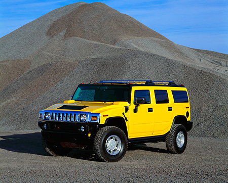 AUT 15 RK0612 02 © Kimball Stock 2003 Hummer H2 Yellow 3/4 Front View By Pile Of Gravel Blue Sky