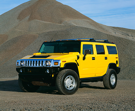 AUT 15 RK0616 03 © Kimball Stock 2003 GM H2 Hummer Yellow 3/4 Front View By Pile Of Gravel Blue Sky