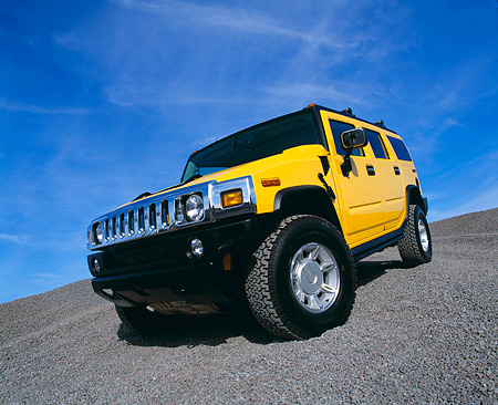AUT 15 RK0621 02 © Kimball Stock 2003 Hummer H2 Yellow 3/4 Front Low View Wide Angle Shot On Gravel Blue Sky