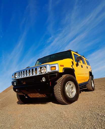 AUT 15 RK0621 05 © Kimball Stock 2003 Hummer H2 Yellow 3/4 Front Low View Wide Angle Shot On Gravel Blue Sky