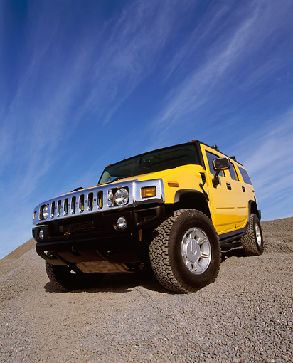AUT 15 RK0621 19 © Kimball Stock 2003 Hummer H2 Yellow 3/4 Front Low View Wide Angle Shot On Gravel Blue Sky