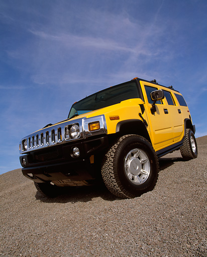 AUT 15 RK0621 22 © Kimball Stock 2003 Hummer H2 Yellow 3/4 Front Low View Wide Angle Shot On Gravel Blue Sky