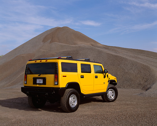 AUT 15 RK0624 03 © Kimball Stock 2003 Hummer H2 Yellow 3/4 Rear View By Pile Of Gravel Blue Sky