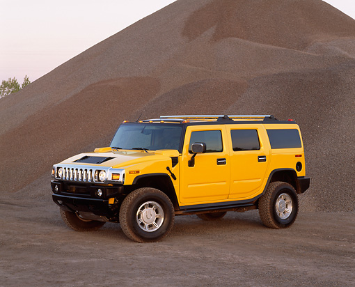 AUT 15 RK0629 02 © Kimball Stock 2003 Hummer H2 Yellow 3/4 Front View By Pile Of Gravel At Dusk