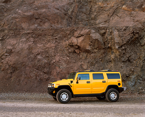 AUT 15 RK0634 01 © Kimball Stock 2003 Hummer H2 Yellow 3/4 Front View By Rock Wall