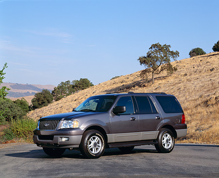 AUT 15 RK0642 02 © Kimball Stock 2003 Ford Expedition XLT Gray 3/4 Front View On Pavement By Dry Grass Hill Blue Sky