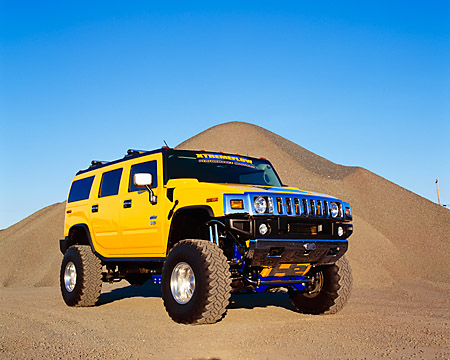 AUT 15 RK0660 03 © Kimball Stock 2003 Hummer H2 Yellow 3/4 Front View On Gravel