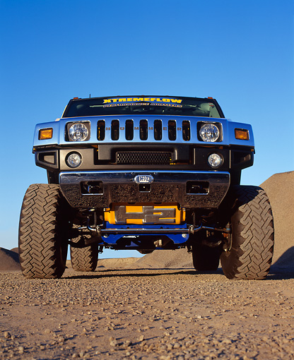 AUT 15 RK0669 01 © Kimball Stock 2003 H2 Hummer Lifted Yellow Low Head On Shot On Dirt Blue Sky