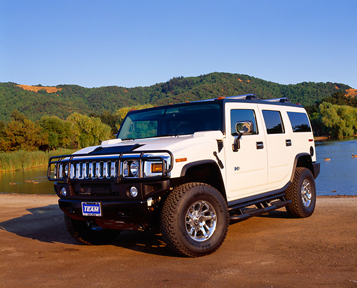 AUT 15 RK0732 05 © Kimball Stock 2003 H2 Hummer White 3/4 Front View On Dirt By Water And Trees
