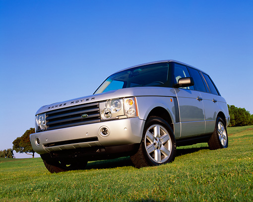 AUT 15 RK0747 03 © Kimball Stock 2004 Land Rover Range Rover HSE Silver Low 3/4 Front View On Grass Blue Sky