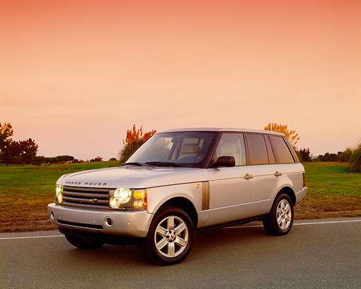 AUT 15 RK0755 02 © Kimball Stock 2004 Land Rover Range Rover HSE Silver Front 3/4 View On Pavement By Grass Filtered