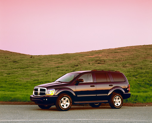 AUT 15 RK0770 01 © Kimball Stock 2004 Dodge Durango Blue 3/4 Side View On Pavement Grass Hill Filtered