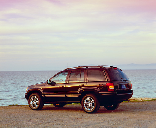 AUT 15 RK0776 02 © Kimball Stock 2004 Jeep Cherokee Limited Burgundy 3/4 Rear View On Sand By Water Filtered