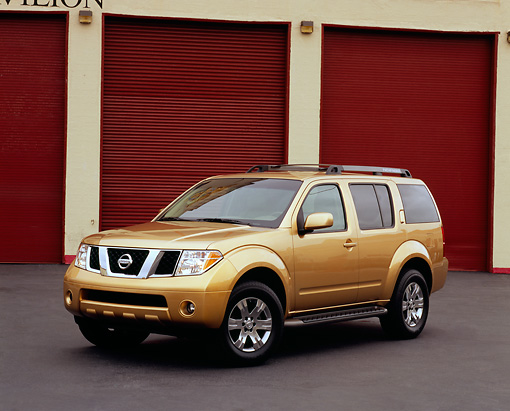 AUT 15 RK0787 01 © Kimball Stock 2005 Nissan Pathfinder Gold Front 3/4 View On Pavement By Garage Doors