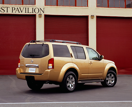 AUT 15 RK0791 01 © Kimball Stock 2005 Nissan Pathfinder Gold Rear 3/4 View On Pavement By Garage Doors