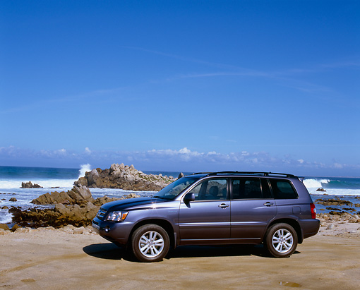 AUT 15 RK0882 02 © Kimball Stock 2006 Toyota Highlander Hybrid Blue 3/4 Front View On Sand By Ocean