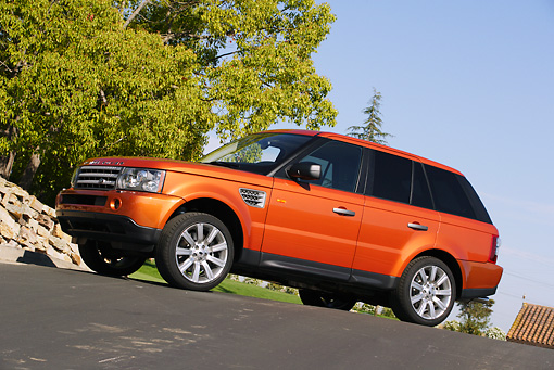 AUT 15 RK0898 01 © Kimball Stock 2006 Land Rover Range Rover Sport Supercharged Orange 3/4 Side View On Pavement By Trees