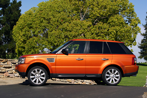 AUT 15 RK0899 01 © Kimball Stock 2006 Land Rover Range Rover Sport Supercharged Orange Profile On Pavement By Tree