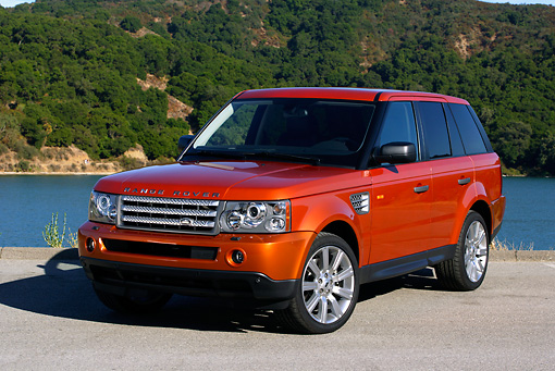 AUT 15 RK0900 01 © Kimball Stock 2006 Land Rover Range Rover Sport Supercharged Orange 3/4 Front View On Pavement By Lake