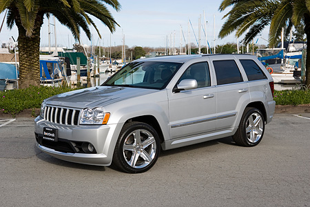AUT 15 RK0933 01 © Kimball Stock 2006 Jeep Grand Cherokee SRT8 Silver 3/4 Front View On Pavement By Harbor And  Palm Trees