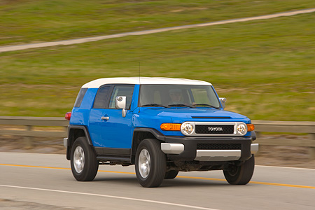 AUT 15 RK0964 01 © Kimball Stock 2007 Toyota FJ Cruiser Blue And White 3/4 Front View On Road By Grass Hills