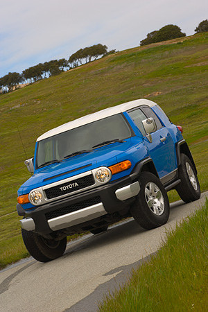 AUT 15 RK0967 01 © Kimball Stock 2007 Toyota FJ Cruiser Blue And White Slanted  3/4 Front View On Pavement By Grass Hills