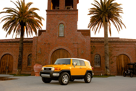 AUT 15 RK1010 01 © Kimball Stock 2007 Toyota FJ Cruiser Yellow And White Low 3/4 Front View On Pavement By Building And Palm Trees