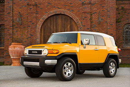 AUT 15 RK1011 01 © Kimball Stock 2007 Toyota FJ Cruiser Yellow And White Low 3/4 Front View On Pavement By Building
