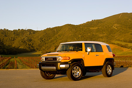 AUT 15 RK1012 01 © Kimball Stock 2007 Toyota FJ Cruiser Yellow And White Low 3/4 Front View On Pavement By Grass Hills