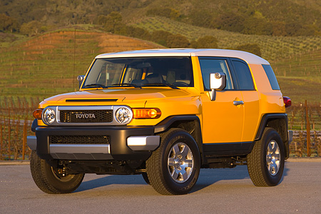 AUT 15 RK1013 01 © Kimball Stock 2007 Toyota FJ Cruiser Yellow And White Low 3/4 Front View On Pavement By Grass Hills