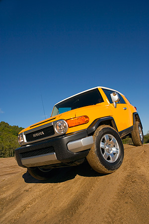 AUT 15 RK1016 01 © Kimball Stock 2007 Toyota FJ Cruiser Yellow And White Low 3/4 Front View On Dirt Hill